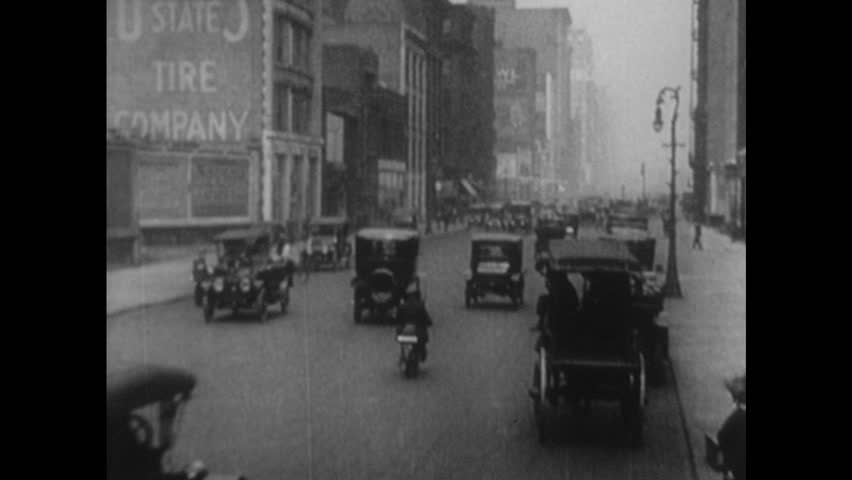 UNITED STATES 1900s: Intertitle / View of city street / Pedestrians, traffic in intersection.