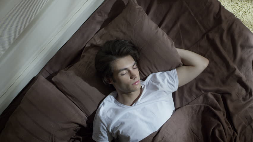 Attractive boy sleeping on a bed. Shot on RED EPIC Cinema Camera.
