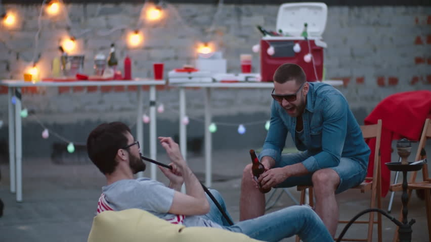 Locked down shot of two male friends men relaxing on rooftop on summer day, talking, drinking beer and smoking hookah