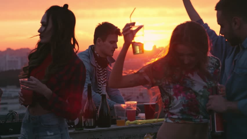 Medium shot of beautiful young couple dancing at sunset rooftop party to the music played by dj, drinking cocktails and beer surrounded by friends
