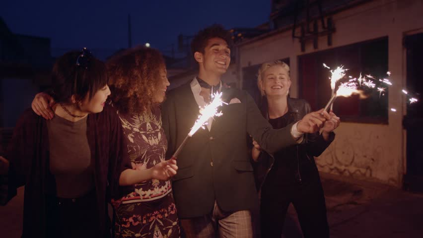 Happy young friends celebrating new years eve with sparklers at night. Best friends hanging out at night and celebrating outdoors.  | Shutterstock HD Video #19109500