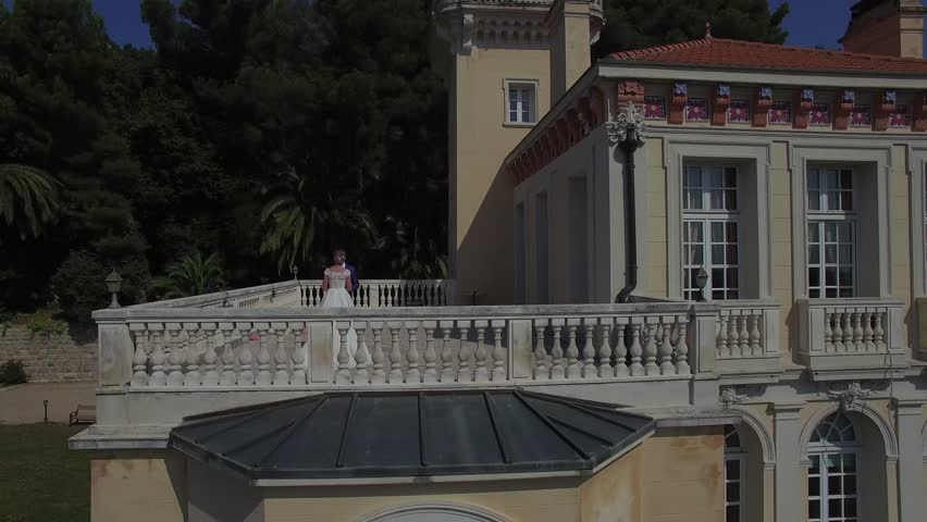 Love couple hold hands stand on balcony beautiful house. Royal family husband wife kiss on terrace of small beautiful chateau in Europe France Grasse mountain area. Wedding reception luxury lifestyle | Shutterstock HD Video #19111090