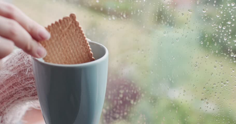 Female Hand Dipping Biscuit in a cup of Hot Coffee or Tea, Rainy Window Background. 4K DCi SLOW MOTION 120 fps. Having Morning coffee with cookie by the window, in rainy spring, winter or autumn day.