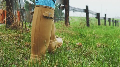 Yellow Rain Boots Walking on a Wet Grass under the Rain. SLOW MOTION 120 fps. Woman walking in the field under the pouring rain, Close Up on Gumboots. Autumn or Spring rainy day.