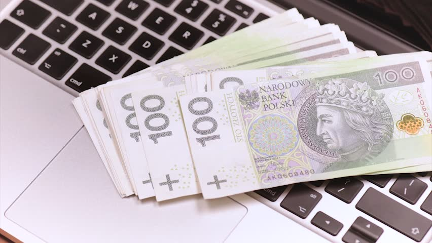 Woman throws the Polish money banknotes on keyboard of laptop computer. Close up of female hand, bills zloty and notebook.
