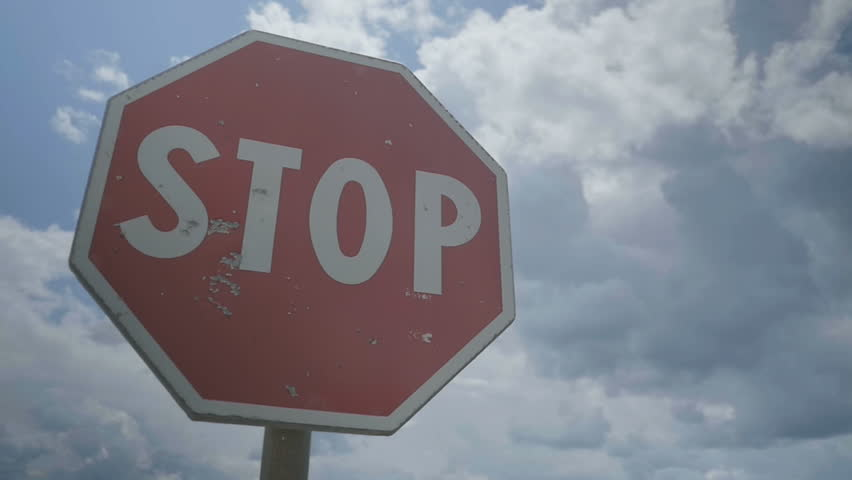 Medium low angle handheld slow motion shot of a red damaged stop sign during a cloudy day.