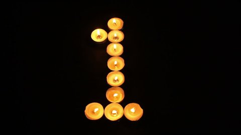 Static shot of burning tealight candles arranged like pixel art numeral digits to represent the number one on a black background.