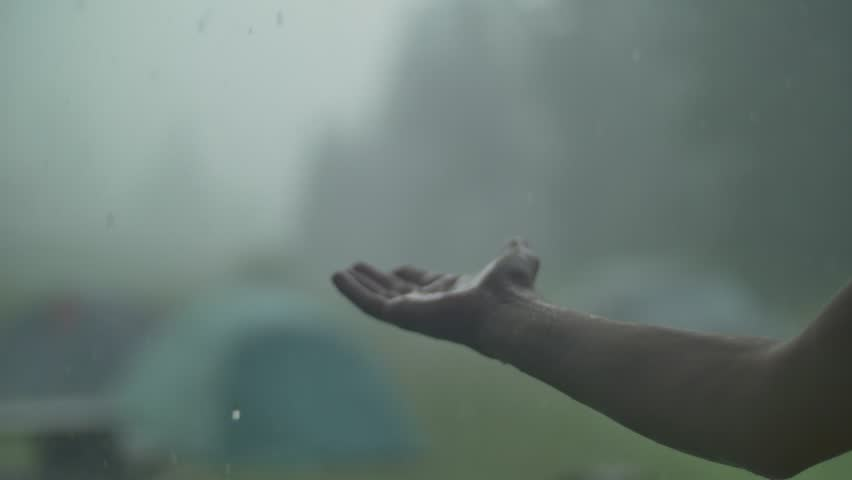 Man hand in the rain and hail