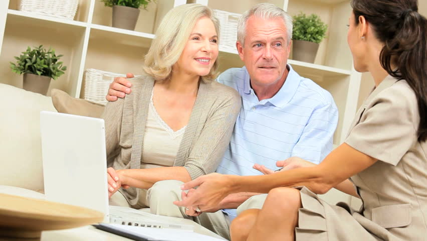Mature caucasian couple having home meeting with female financial advisor