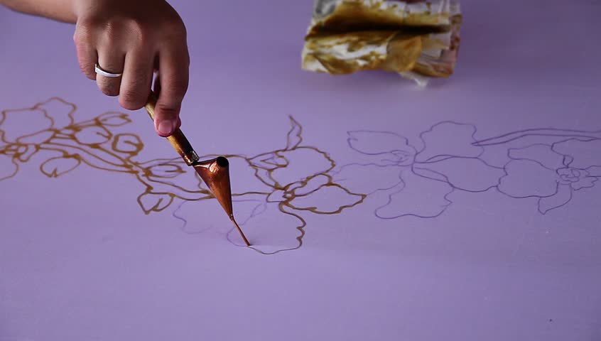 An artist carefully draw the flower motif on traditional batik fabric with melted wax