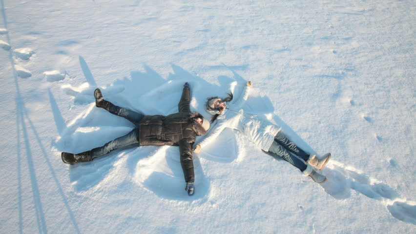 Young couple lying on snow and making snow angels