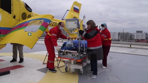 KRASNODAR, RUSSIA - MARCH 20: ROOF OF REGIONAL KUBAN HOSPITAL CLINIC #1. DEMONSTRATION OF EMERGENCY MEDICAL SERVICE. USING AIR AMBULANCE HELICOPTER. TEAM OF DOCTORS PUSHING STRETCHER ON MARCH 20, 2016