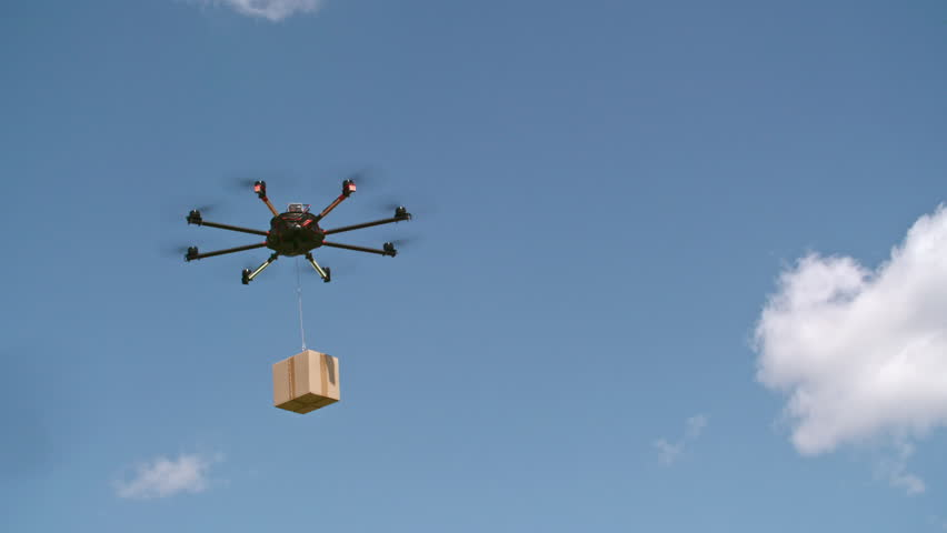 Low angle view of drone flying through the air and carrying post package