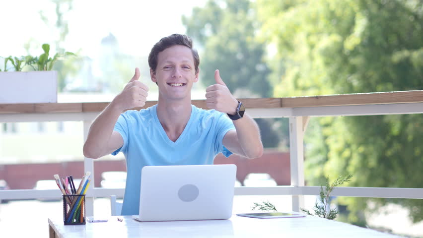 Thumbs Up by Young Man at Work, Sitting on Desk, Outdoor   Shutterstock HD Video #19227460