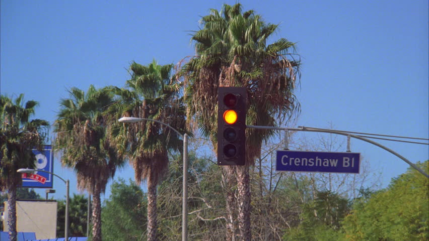 day Traffic signal turns yellow red street sign Crenshaw Bl. palm trees background Los Angeles
