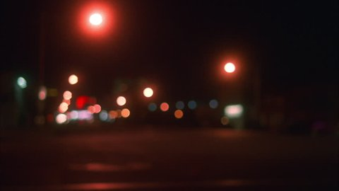 Night Rack from soft focus hold deserted empty dark city street car headlights camera then pan right white Cadillac sedan small town deserted street