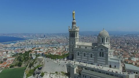 MARSEILLE, FRANCE - JUL 31, 2016: Panorama of city on sea shore and edifice of Notre Dame de la Garde at summer sunny day. Aerial view