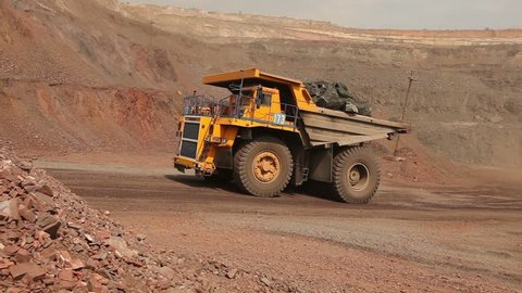 big yellow truck in a career of iron ore mining, delivery by the motor transport of iron ore from a pit, pit iron ore,