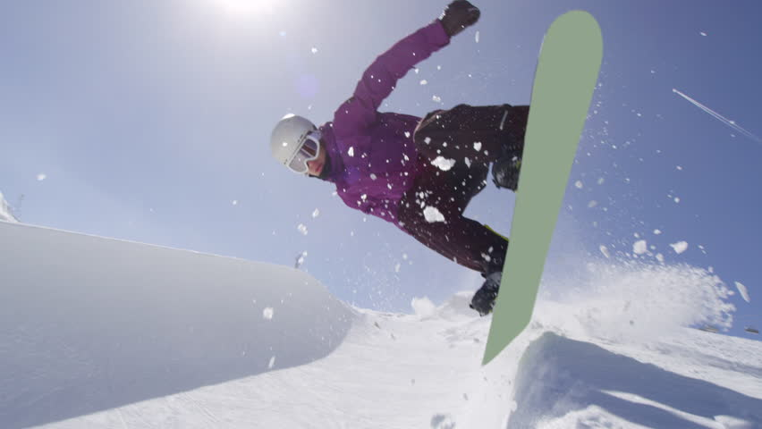 SLOW MOTION: Young pro snowboarder riding the half pipe in big mountain snow park, sliding and spraying on the halfpipe wall in sunny winter