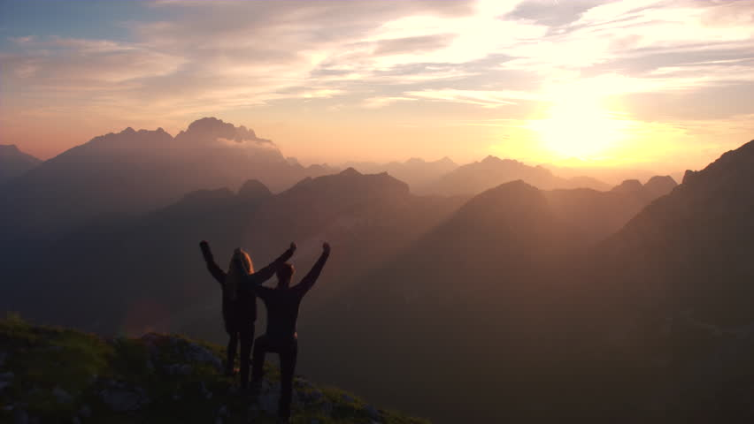 Aerial - Flyover silhouette of a couple with raised arms celebrating successful climb on the mountain in beautiful sunset | Shutterstock HD Video #19249198