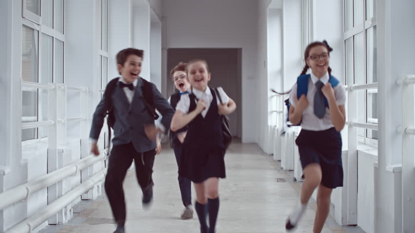 Lockdown of four excited laughing schoolgirls and schoolboys wearing uniform and backpacks jumping up and running along school hallway towards camera