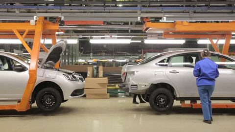 People work at assembly of cars on conveyor of factory