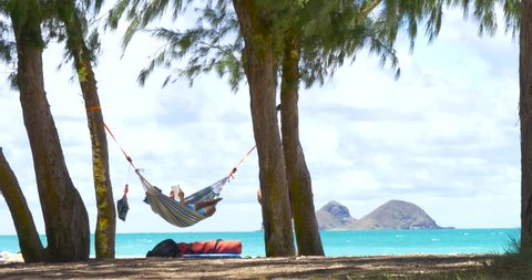 Young man reading a book on hammock exotic beach. Man in hammock is relaxing on tropical beach.