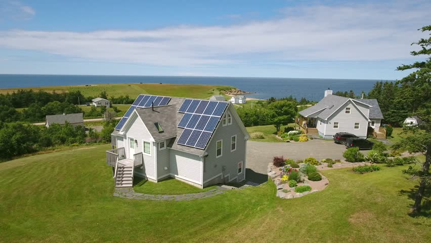 An aerial shot of solar panels on a cottage in Cape Breton Nova Scotia Canada on the rugged ocean coastline