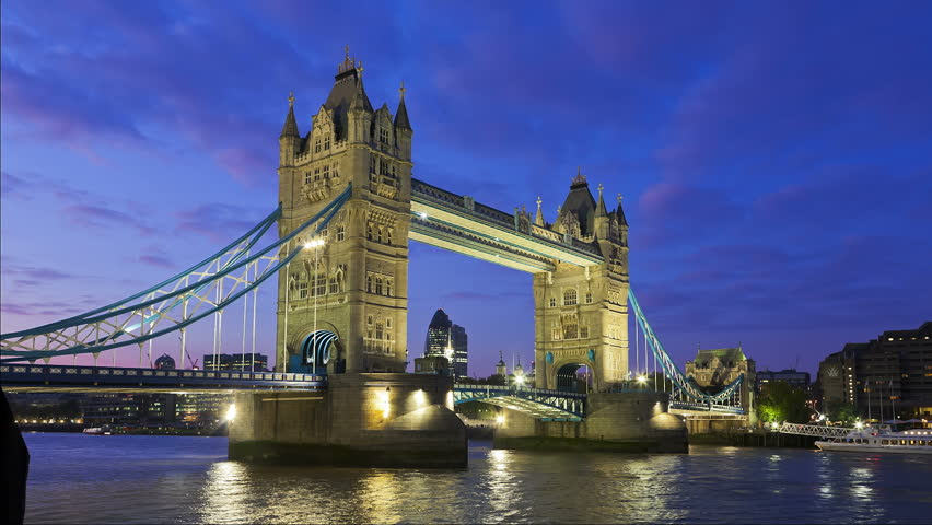 Tower Bridge in London at night being open  for passing underneath boat, London, United Kingdom. Time lapse footage of boat on Thames River with City of London lights in the background. #1927135