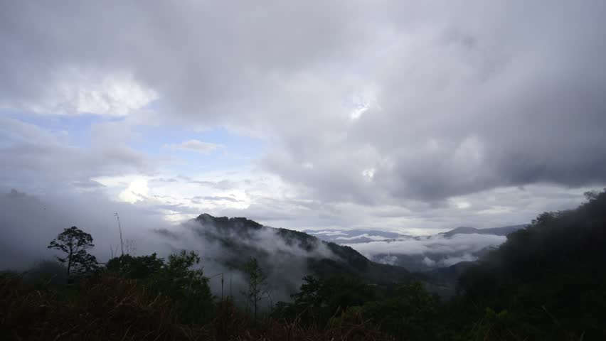 Time lapse of dramatic cloudy sky with rolling white mist over hilly landscape valley of beautiful Sabah Malaysian Borneo.