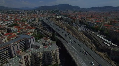 4K Nice city highway road traffic France aerial view from above. Fly over multiple lane motorway and train station in Nice Europe urban landscape with mountains background. Busy big city life concept