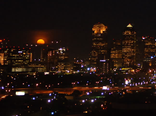 Timelapse of full moon rising over Dallas Texas downtown skyline. Car traffic zooming by on the interstate.