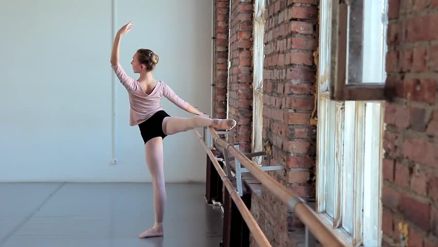 Young graceful female ballet dancer in training clothes exercising in ballet class
