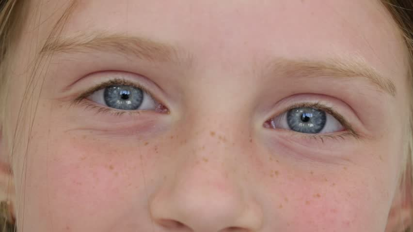 Close up young girl eyes, she stares into camera, portrait children, macro, indoors