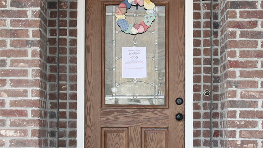 Eviction Notice Taped On Front Door Of House As Home Owner