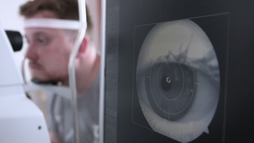 Male patient on a eye examination. Medical attendance at the optometrist in a bright modern clinic.