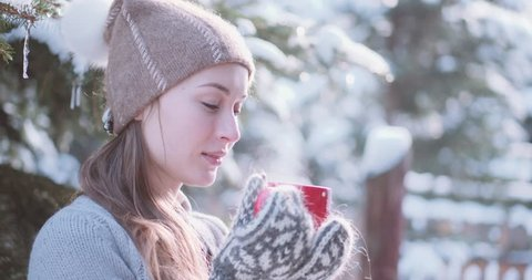 Woman Drinks Hot Tea or Coffee From a Cozy Cup on Snowy Winter Morning Outdoors. 4K DCi SLOW MOTION 120 fps. Beautiful Girl Enjoying Winter in a Garden with a Mug of Warm Drink. Christmas Holidays