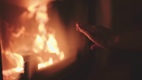 Woman Rubbing Hands in front of Burning Fireplace, 4K Close Up. Girl is warming cold hands during autumn or winter in front of fire. Comfort of Home.