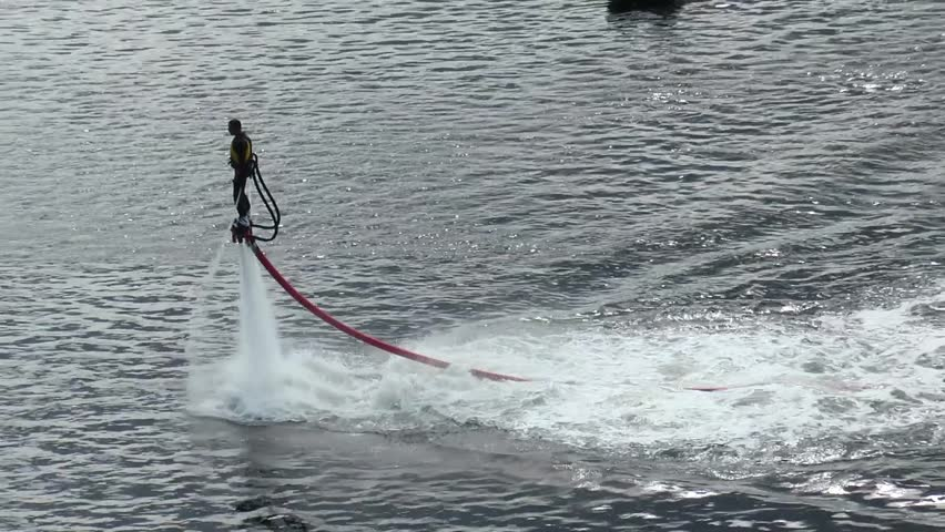 Murmansk, RUSSIA - June 29, 2013. Festival, the Murmansk mile. Athlete on the flyboard flying and dives into the water with solar flares. | Shutterstock HD Video #19354360