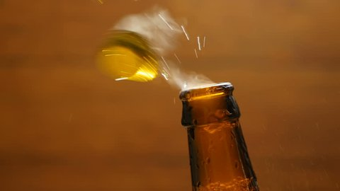 Opening cold bottle of beer with steam and spray (close-up)