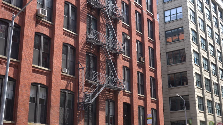 DX establishing shot of an urban brick apartment building in city. Fire escape surrounds the structure for resident safety. Day time exterior