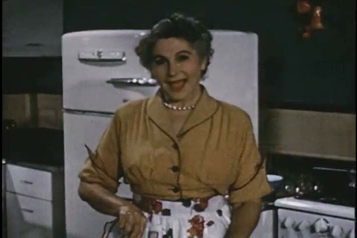 A woman shows off the frozen fruit she uses to make jelly in 1951. (1950s)