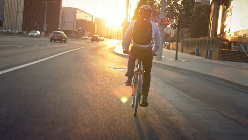 Commuter riding a bike on his morning travel to job. Smartly dressed active young man traveling to job in the city early in the morning. Sunrise in front of the cyclist. | Shutterstock Video #19441258