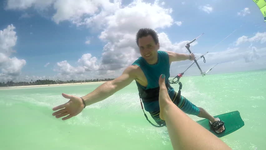 SLOW MOTION: Smiling young kiter kitesurfing and high five slapping in turquoise ocean on sunny day. Cheerful kiteboarder man kiting in beautiful tropical sandy beach lagoon on summer vacation