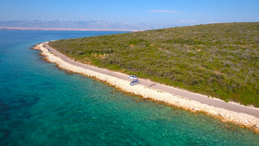 White car driving next to sea beach aerial view 4K. Family travel to sea vacation in white van, driving near sea with forest in background. Tracking vehicle from air.