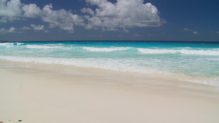 ... waves landing on sandy beach ...