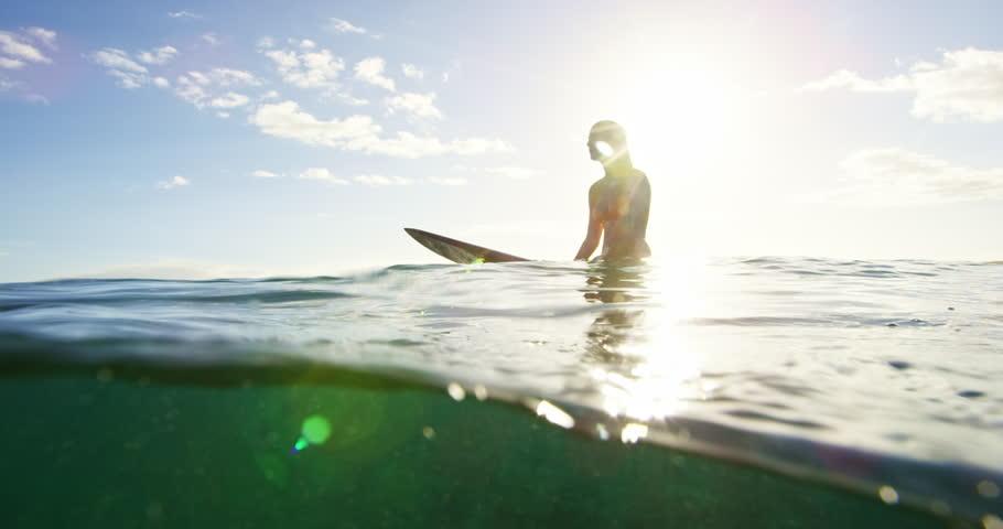 Beautiful surfer girl enjoying sunset surf