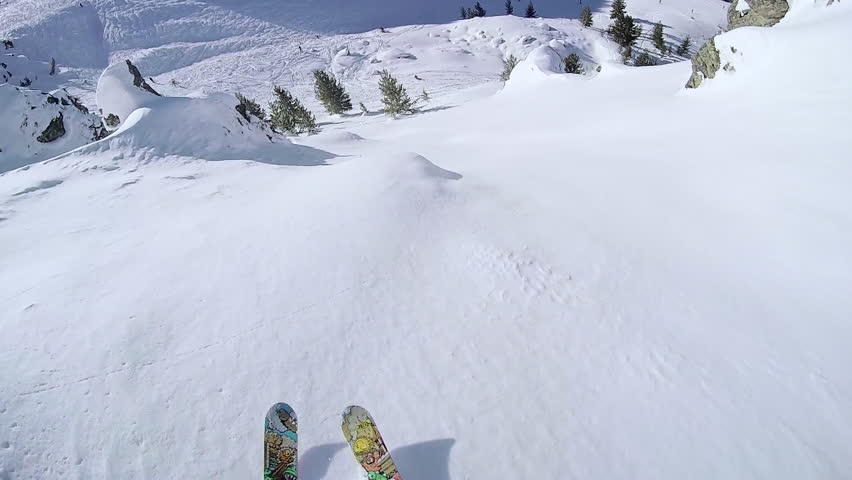 FIRST PERSON VIEW CLOSE UP: Unrecognizable skier riding fresh powder snow down the steep mountain slope, jumping over rocky overhang. Freeride skier skiing in backcountry mountain ski resort | Shutterstock HD Video #19548277