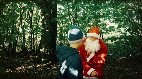 in the Early Autumn the Boy Scoffs at Santa - Beats Him and Pulls Clothes.santa boy tormented and hurt him, he was a sadist. green leaves and forest behind grieving Santa