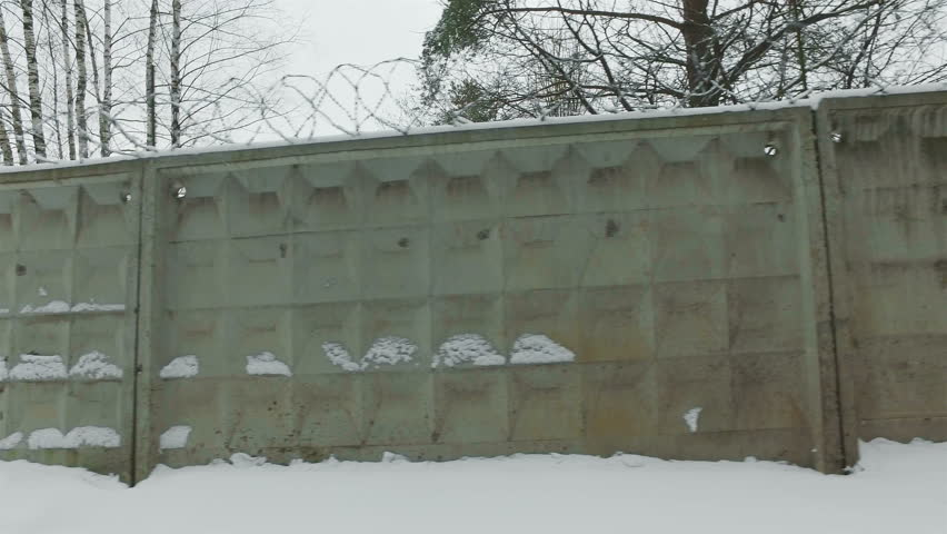 concrete fence with barbed wire. Wall with barbed wire